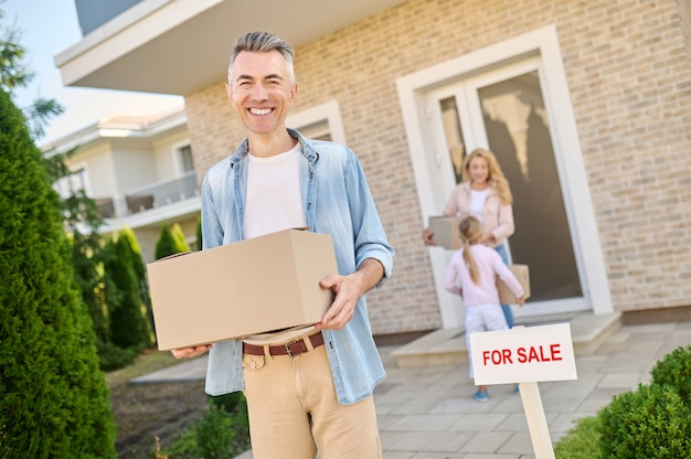 Smiling man taking the box out of house