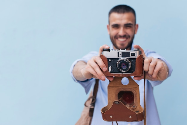 Smiling man taking photo with retro camera standing against blue wall