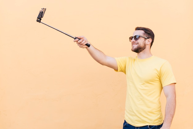 Smiling man taking selfie on cell phone standing near peach wall