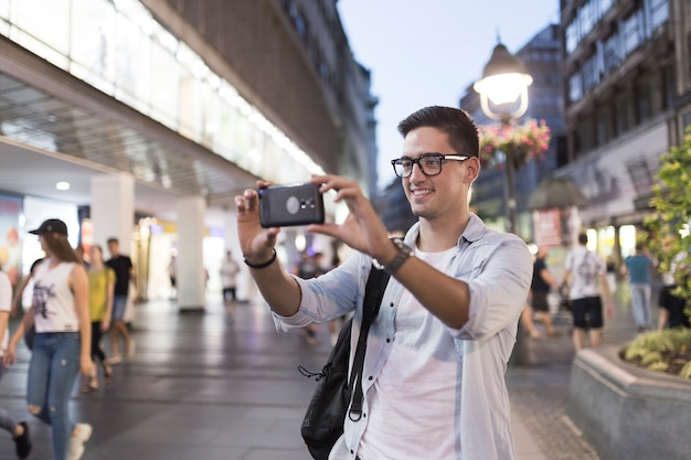 Smiling man taking selfie from mobile phone