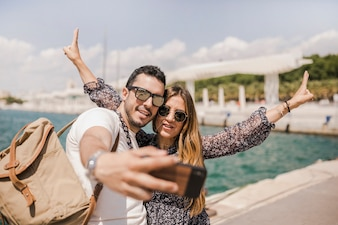 Smiling man taking selfie on cell phone with her girlfriend gesturing