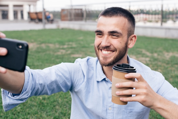 Smiling man taking selfie while holding disposable coffee cup at park