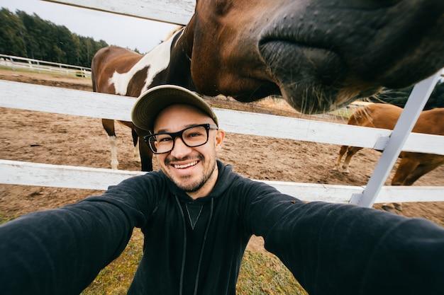 彼の後ろに馬の銃口でselfieを取って笑顔の男
