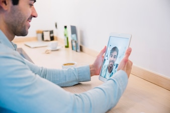 Smiling man taking selfie with tablet