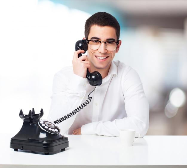 Uomo sorridente che comunica su un telefono nero
