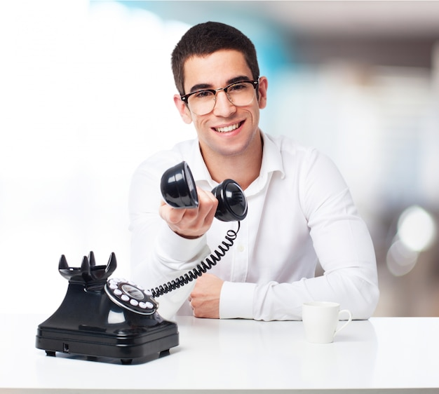Smiling man talking on a black phone