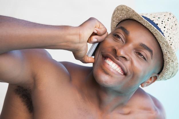 Улыбающийся человек разговаривает по телефону у бассейна