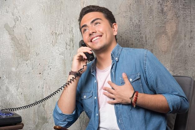 電話で話し、椅子に座っている笑顔の男。高品質の写真