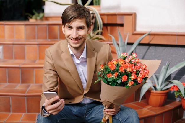 彼の手で携帯電話を見ながら笑みを浮かべて男のテキストメッセージ