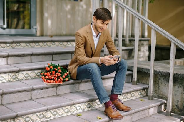 電話を見ながら笑みを浮かべて男のテキストメッセージ