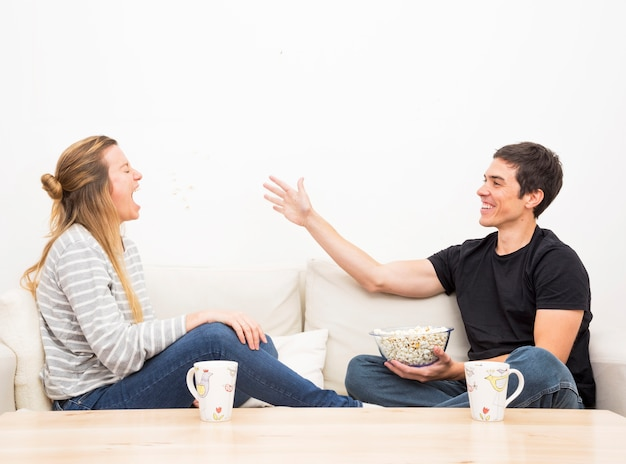 Smiling man throwing popcorn in her girlfriend's mouth