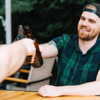 Smiling man toasting beer bottles with his friend