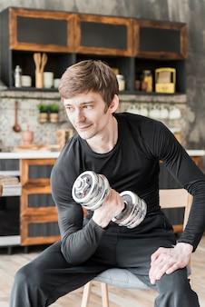 Smiling man training with dumbbell