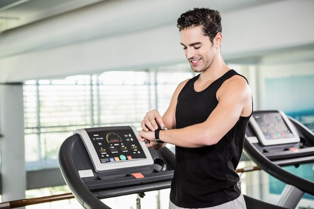 Smiling man on treadmill using smart watch at the gym