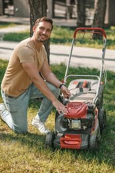 芝刈り機をオンにする笑顔の男