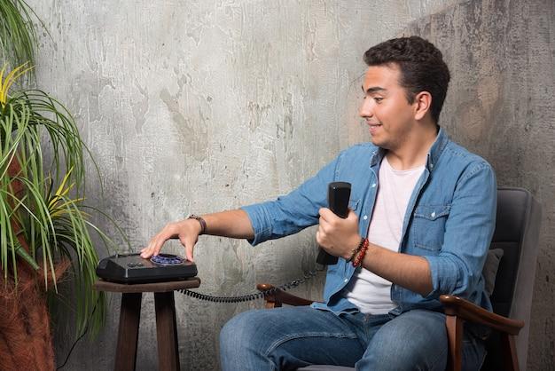 電話で番号を入力し、椅子に座っている笑顔の男。高品質の写真