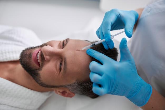 Улыбающийся человек проходит процедуру лифтинга кожи, лежа на диване