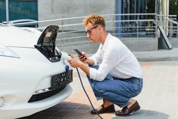 Улыбающийся человек отключает зарядное устройство от машины