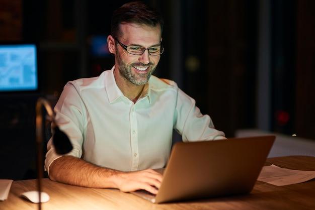 밤에 노트북을 사용하는 웃는 남자