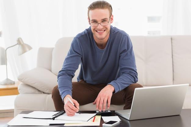 Smiling man using calculator counting his bills