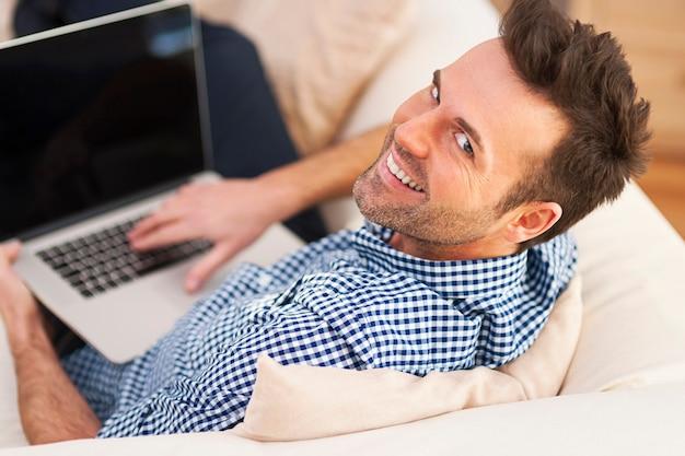 Uomo sorridente utilizzando il computer in soggiorno