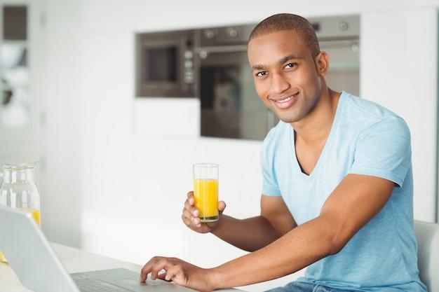 笑みを浮かべて男のラップトップを使用して、台所でオレンジジュースを飲む
