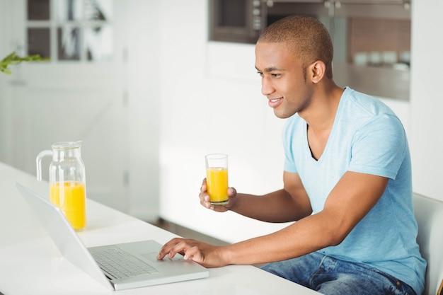 笑みを浮かべて男のラップトップを使用して、ktichenでオレンジジュースを飲む