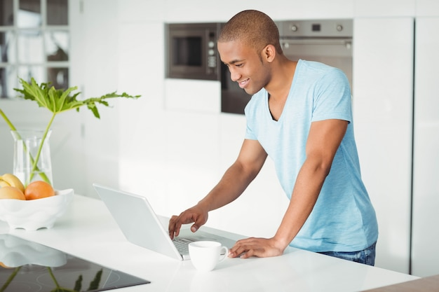 Smiling man using laptop on the counter in kitchen
