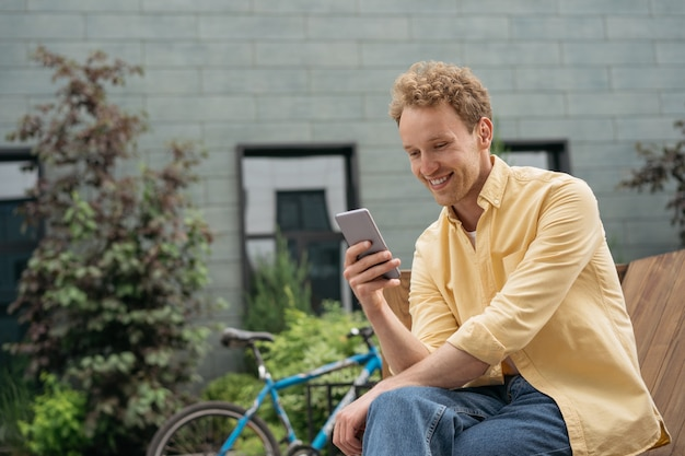 Smiling man using mobile phone shopping online young happy freelancer receive payment ecommerce