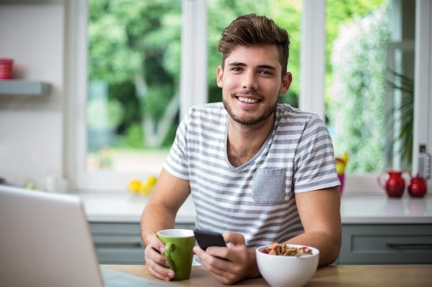 Smiling man using phone while having coffee