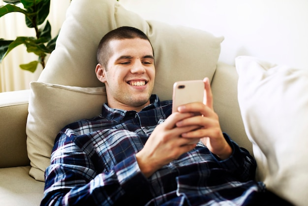 Smiling man using a smartphone at home