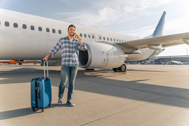 Smiling man using smartphone near airplane outdoor