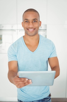 Smiling man using tablet in the kitchen