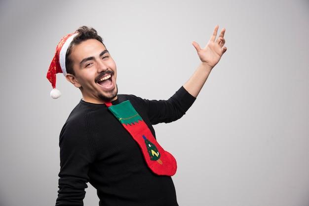 Улыбающийся человек в рождественской футболке и позирует.