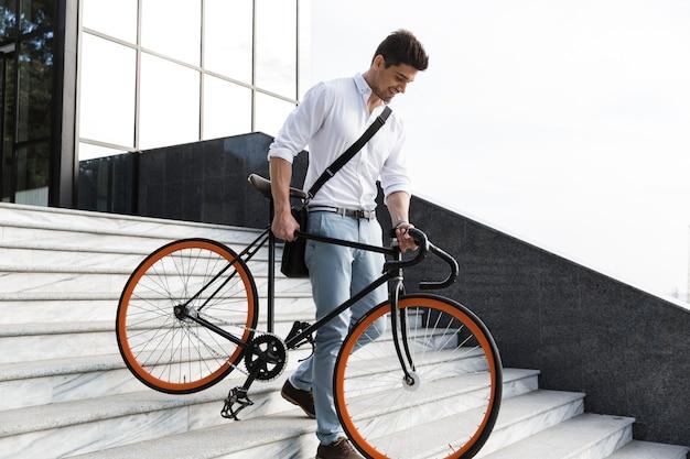 공식적인 옷을 입고 웃는 남자, 도시 거리에서 자전거와 함께 아래층 산책