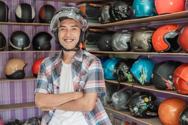 ヘルメットディスプレイラックの背景に交差した手でヘルメットを着用して笑顔