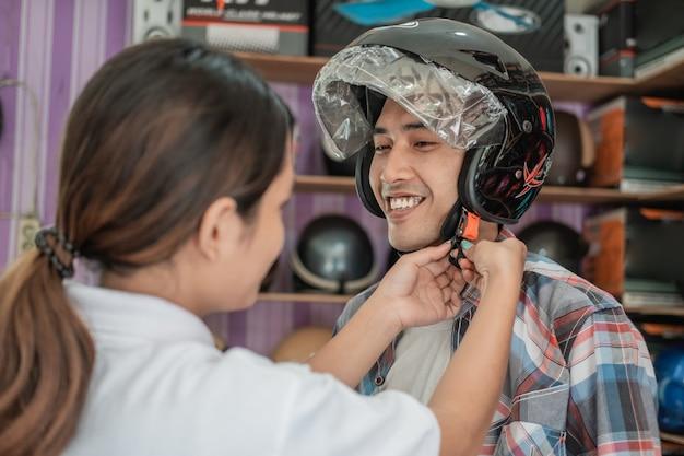 ヘルメットディスプレイラックの背景に店員の助けを借りてヘルメットをかぶって笑顔の男
