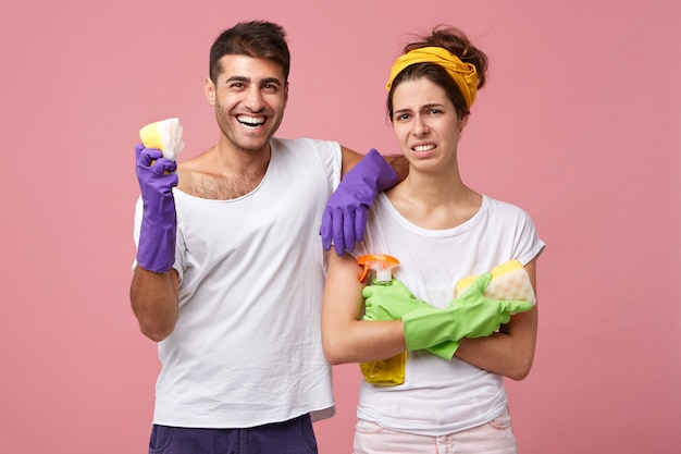 Smiling man wearing protective gloves and white t-shirt holding sponge in hand leaning at his pretty wife who is dissatisfied not wanting to do cleaning standing crossed hands having frowning face