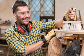 Smiling man wearing safety glasses and ear defender around his neck cleaning wooden plank with brush