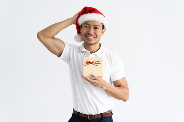 Smiling man wearing santa hat and holding gift box