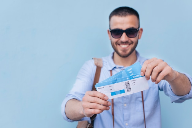 Smiling man wearing sunglasses showing air ticket on blue background