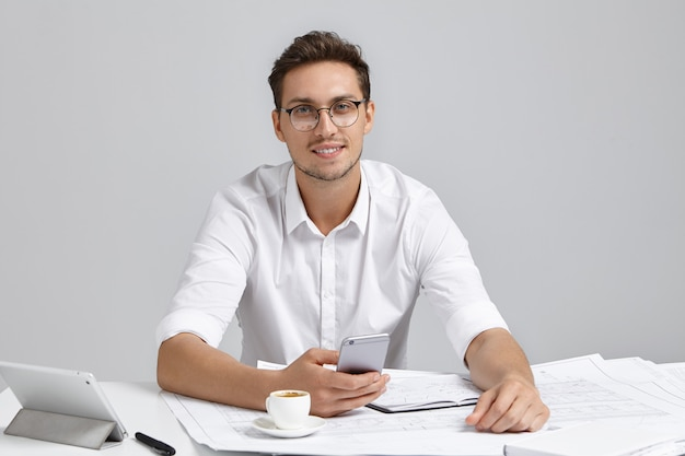 Smiling man wears white formal shirt and round spectacles, holds mobile phone, messages, drinks coffee, writes sketches, has positive expression. well educated designer uses modern technologies