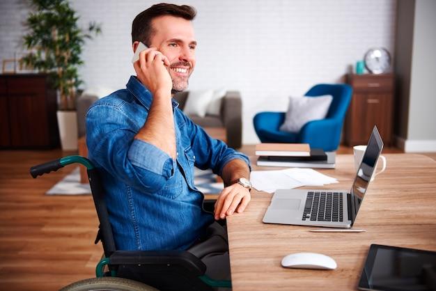 Uomo sorridente su sedia a rotelle che parla al cellulare in ufficio a casa