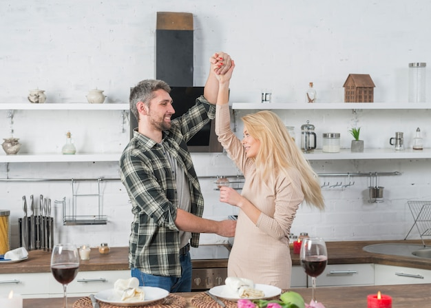 Smiling man whirling woman near table in kitchen