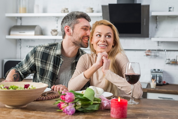 Smiling man whispering to woman and sitting at table in kitchen