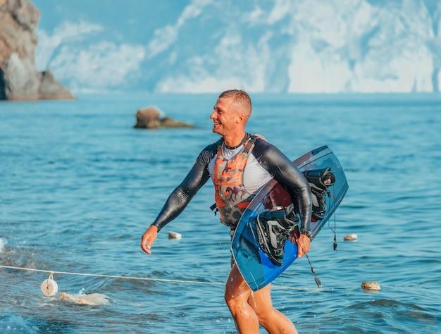 ビーチでのウェイクサーフィンのためのボードと笑みを浮かべて男