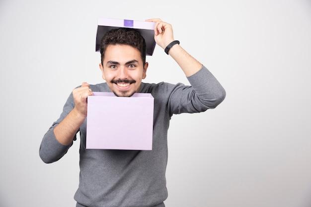 白い壁の上に開いた紫色の箱を持つ笑顔の男。
