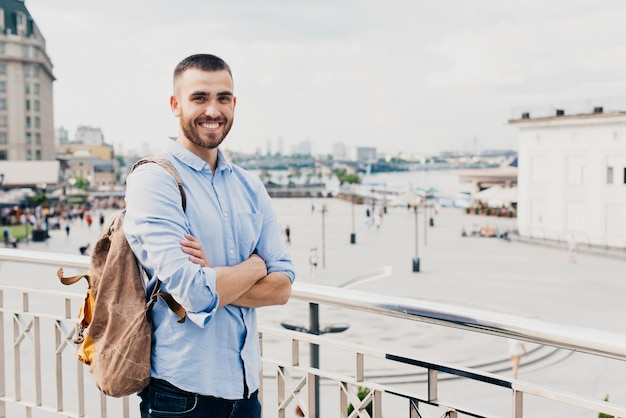 Smiling man with arm crossed standing near railing looking at camera
