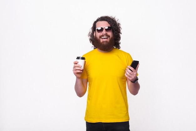 Улыбающийся человек с бородой в желтой футболке с чашкой кофе и смартфоном