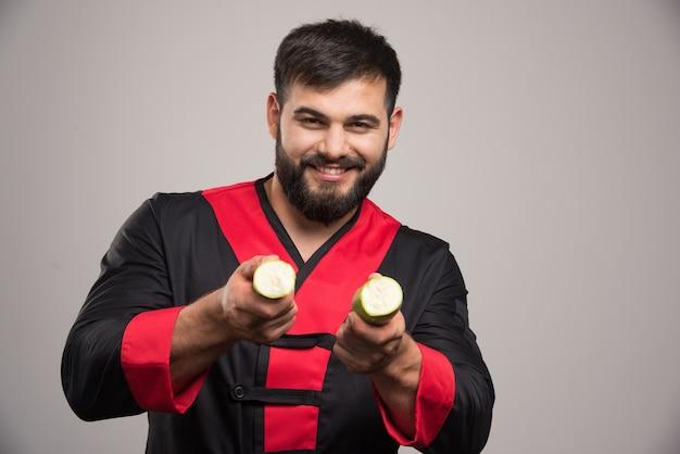 ズッキーニの2つのスライスを示すひげを持つ笑顔の男。